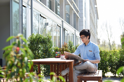 man reading newspaper in backyard of apartment