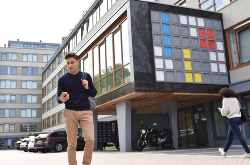 busy student walking past residential building
