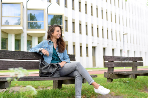 woman sitting on bench next to residential building utrecht