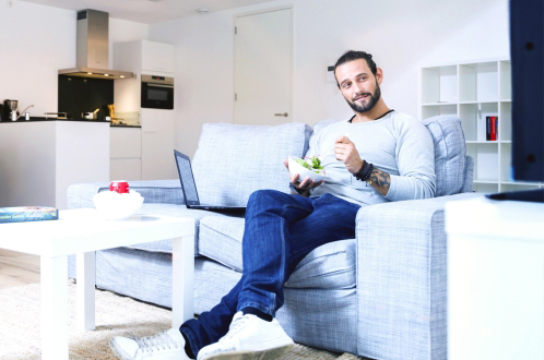 man having breakfast on couch in modern apartment