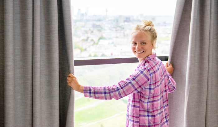 tenant opening the curtains in residence Holland2Stay